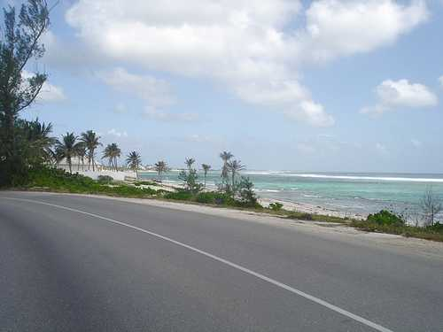 Grand Cayman roadway bending around blue-green Caribbean Bay